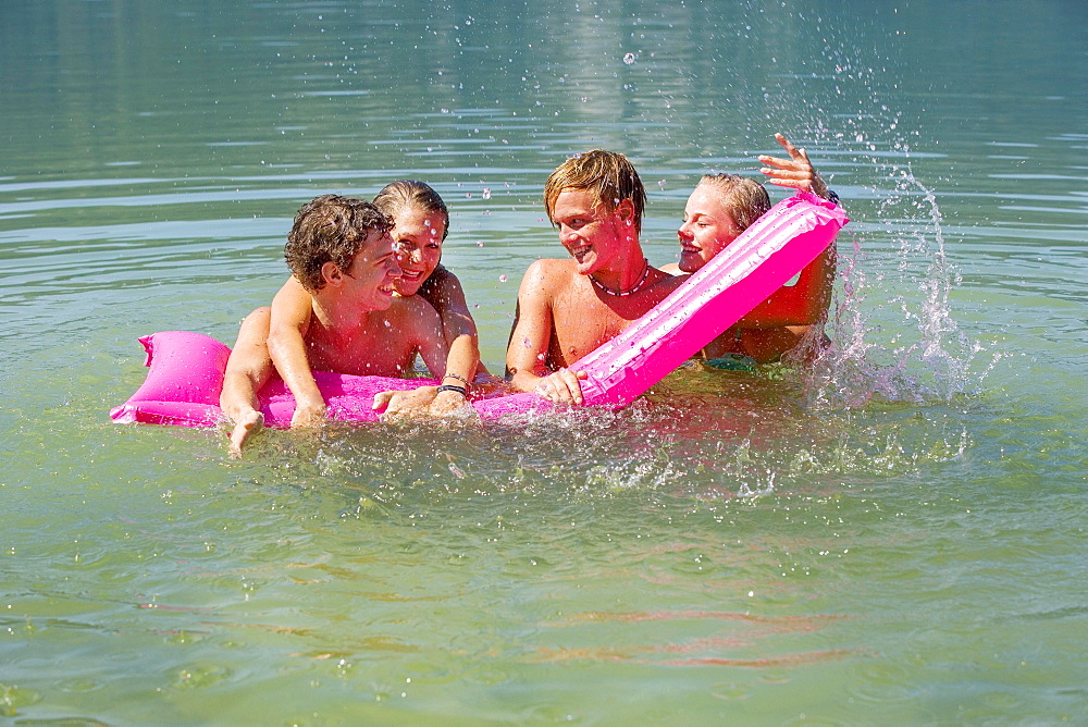 Four teenagers on an air mattress in water have fun bathing, 18 years, Mondsee, Upper Austria, Austria, Europe