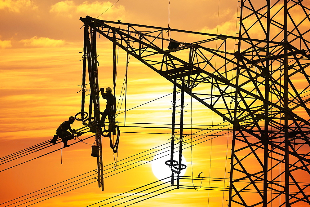 High voltage fitters working on the high voltage pylon at sunset, Baden-Wuerttemberg, Germany, Europe - 832-387795