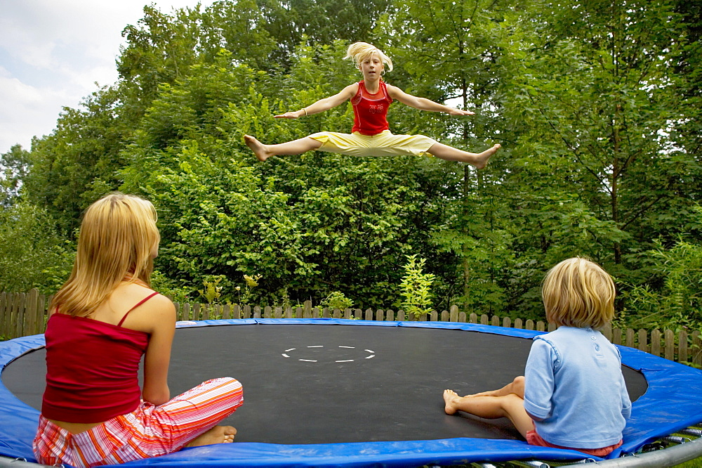 Girls jumping on the trampoline in the garden, Austria, Europe