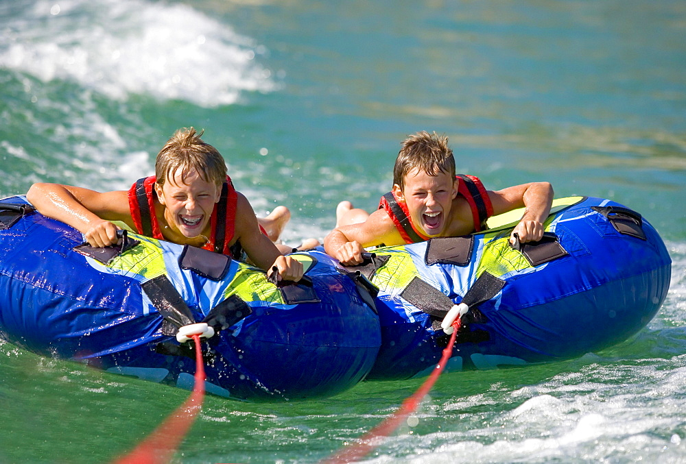 Two children, teenagers rafting with water tyres in a lake, Lake Mondsee, Upper Austria, Austria, Europe