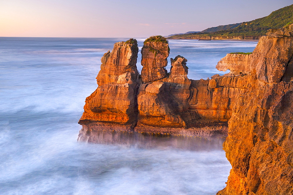 Rock formations on the coast of Paparoa National Park in red evening sun, Punakaiki, Runanga, West Coast, New Zealand, Oceania