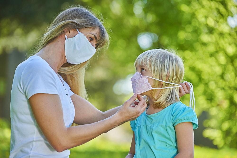 Mutter legt Tochter Mundschutzmaske an, Stadtpark, Corona-Krise, Regensburg, Bayern, Deutschland
