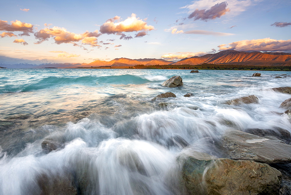 Stones on shore, lake with sunset swell, long time exposure, Lake Tekapo, Canterbury, South Island, New Zealand, Oceania