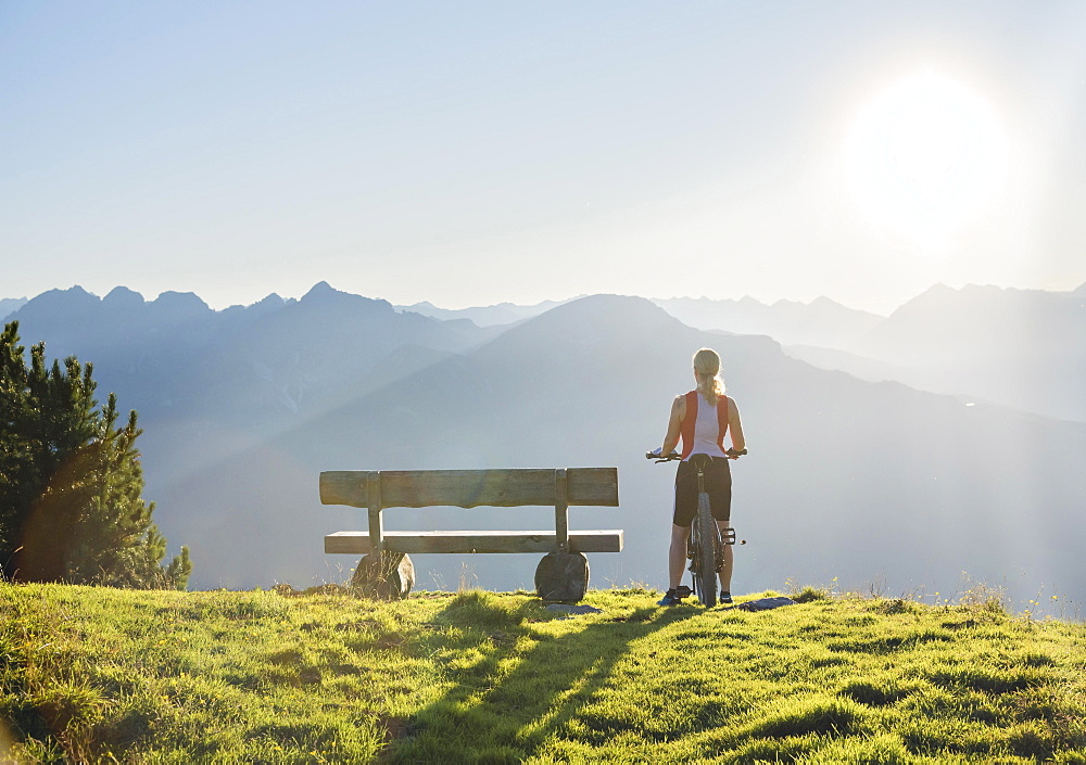 Mountain biker stands with MTB next to a wooden bench and looks into the wide light-flooded mountain landscape, Patscherkofel, Patsch, Tyrol, Austria, Europe - 832-388152