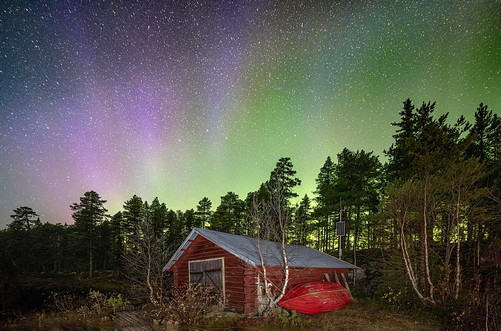 Northern lights above a wooden cabin in a Nordic forest, Jokkmokk, Norrbottens laen, Sweden, Europe