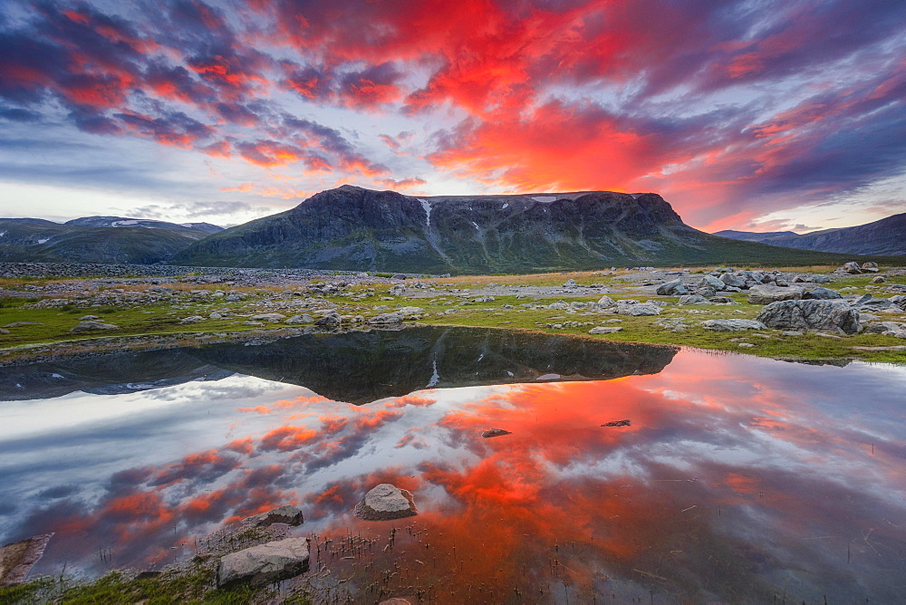 Mountain range reflected in the lake in evening mood with red clouds, Gaellivare, Norrbottens laen, Sweden, Europe
