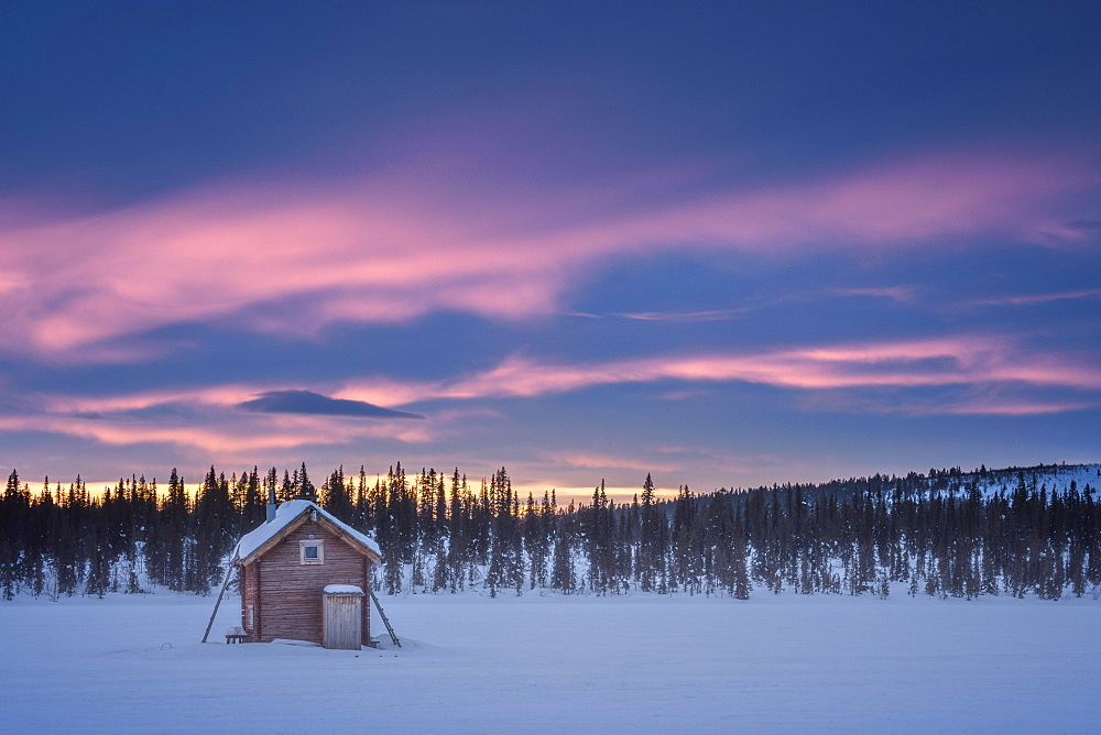 Small wooden hut on a wide snow-covered plain at extremely low temperatures at dawn, Skaulo, Norrbottens laen, Sweden, Europe