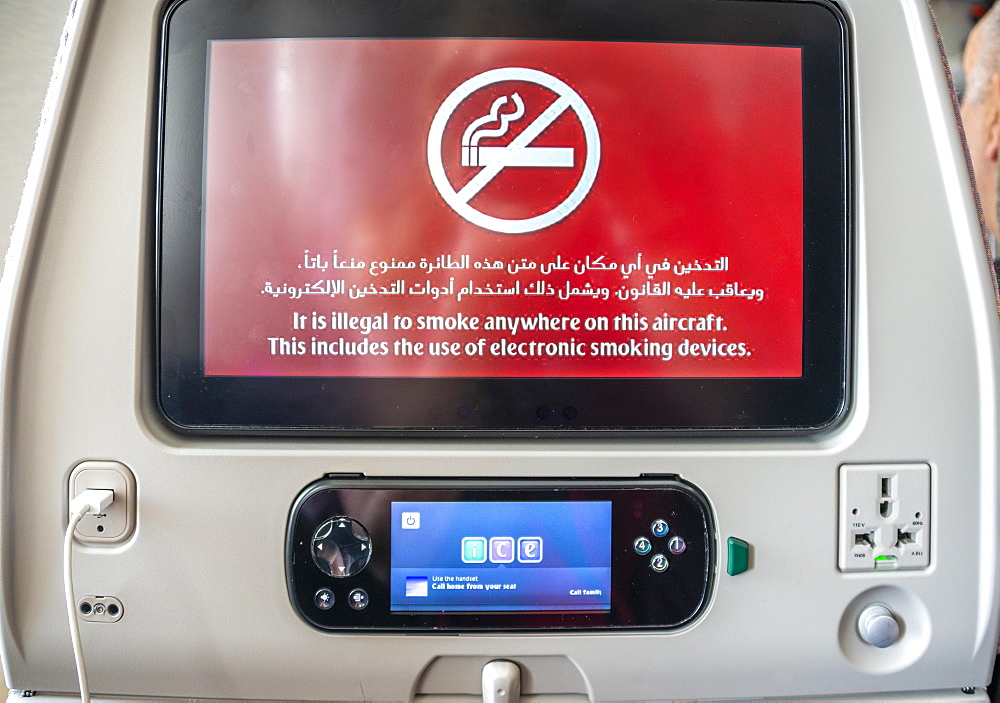 Screen with display smoking ban in Arabic and English on backrest in aircraft, Emirates airline, interior, Dubai, United Arab Emirates, Asia