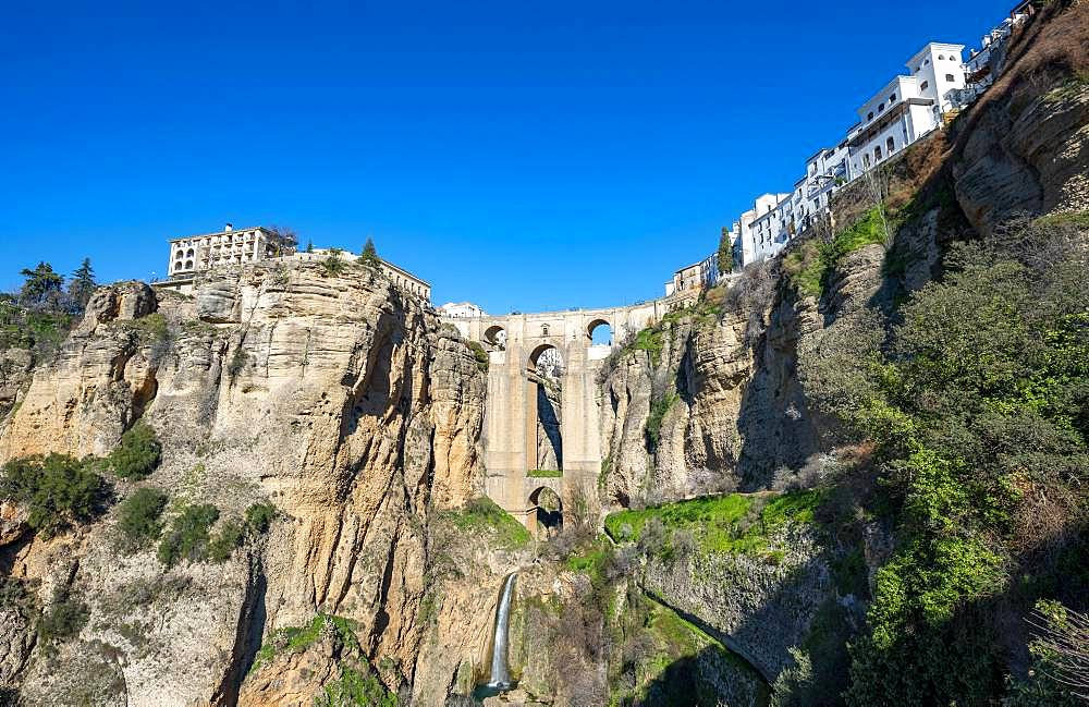 Bridge Puente Nuevo with waterfall at steep cliffs, Tajo gorge and river Rio Guadalevin, Ronda, province of Malaga, Andalusia, Spain, Europe