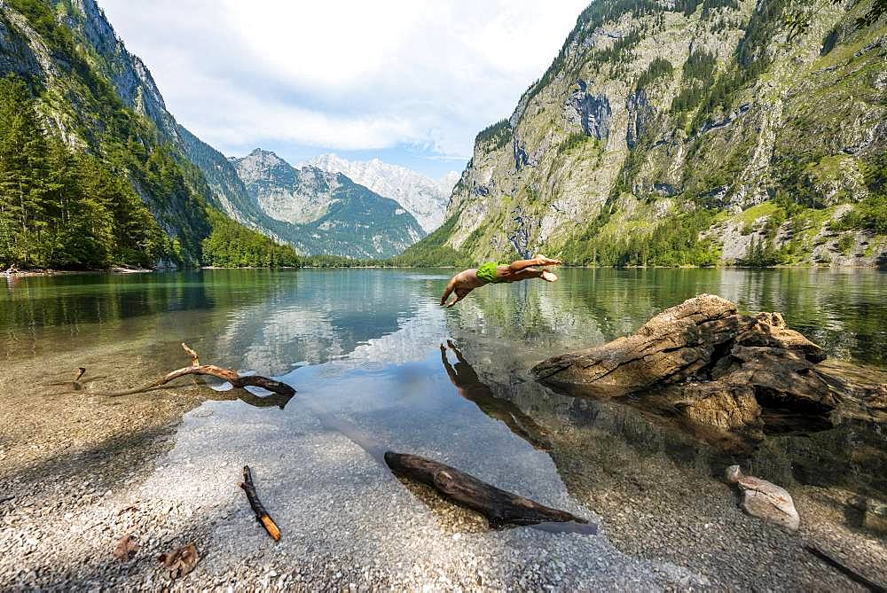 Young man jumps into lake, bathes in mountain lake, mountains are reflected in Obersee, behind Watzmann, salet at Koenigssee, Berchtesgaden National Park, Berchtesgadener Land, Upper Bavaria, Bavaria, Germany, Europe - 832-389462