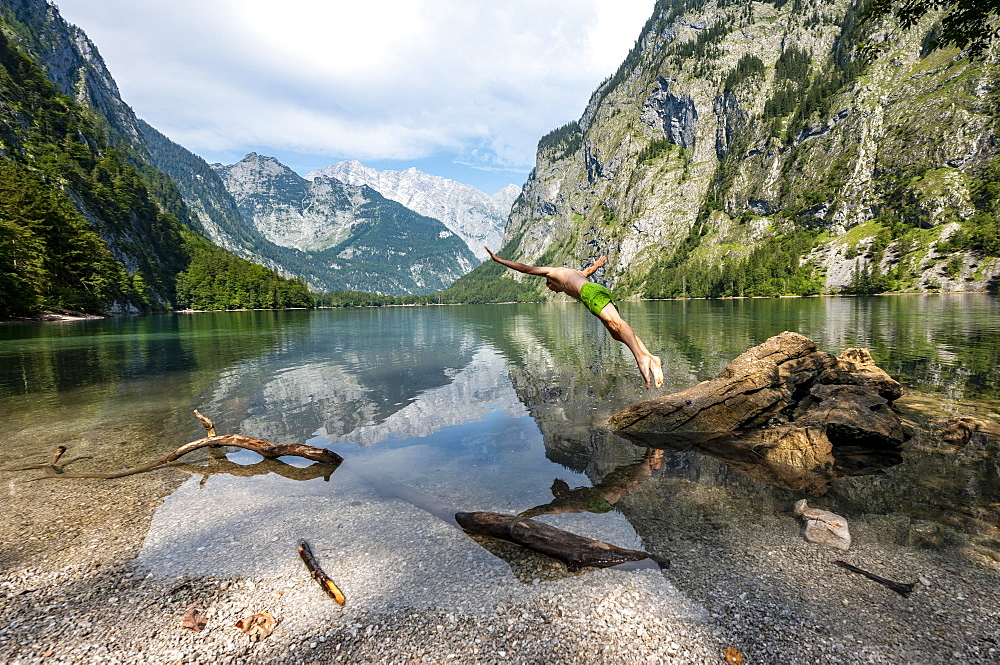 Young man jumps into lake, bathes in mountain lake, mountains are reflected in Obersee, behind Watzmann, salet at Koenigssee, Berchtesgaden National Park, Berchtesgadener Land, Upper Bavaria, Bavaria, Germany, Europe - 832-389463