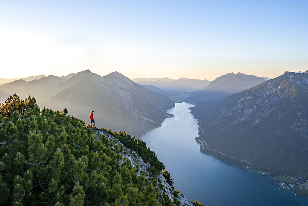 Young man looking over mountain landscape, view from the top of the Baerenkopf to the Achensee, left Seekarspitze and Seebergspitze, Karwendel, Tyrol, Austria, Europe - 832-389487