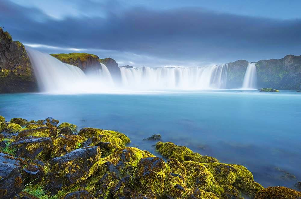 Long time exposure of a turquoise waterfall in volcanic landscape with dramatic clouds and green moss on rocks, Godafoss, Pingeyjarsveit, Norourland eystra, Iceland, Europe - 832-389505