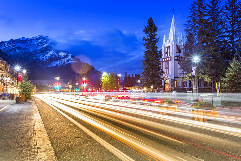 Trail lights on Banff Avenue and St. Paul's Presbyterian Church, Snow Peak visible through clouds, Banff, Banff National Park, Alberta, Canada, North America