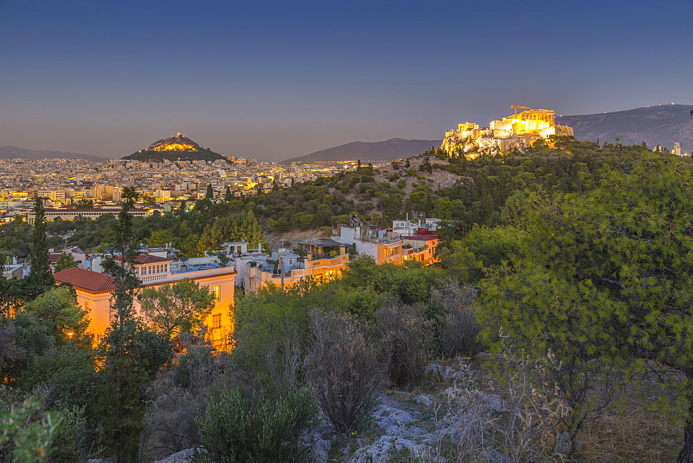 View of The Acropolis and Likavitos Hill at dusk from Filopappou Hill, Athens, Greece, Europe