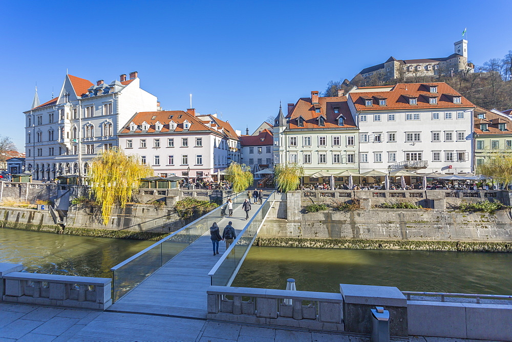 View of buildings along Ljubljana River and Castle visible in background, Ljubljana, Slovenia, Europe