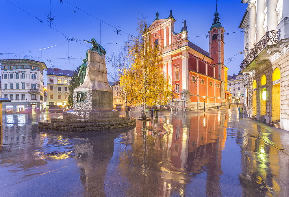 Ornate facade of Franciscan Church of the Annunciation and Prešeren Monument in Plaza Prěsernov refections at dusk, Ljubljana, Slovenia, Europe