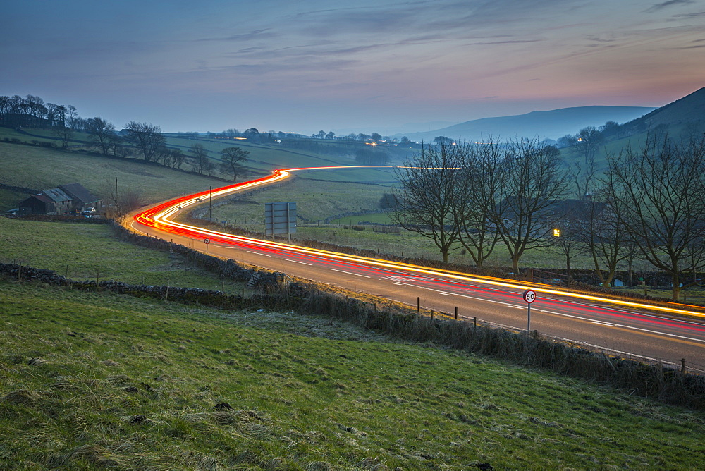 View of vehicle trail lights on A623 at Sparrowpit at dusk, Peak District National Park, Derbyshire, England, United Kingdome, Europe