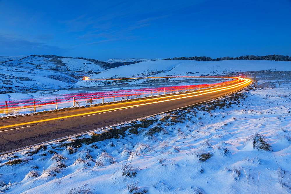 View of trail lights on frozen landscape near Buxton at dusk, High Peak, Derbyshire, England, United Kingdom, Europe