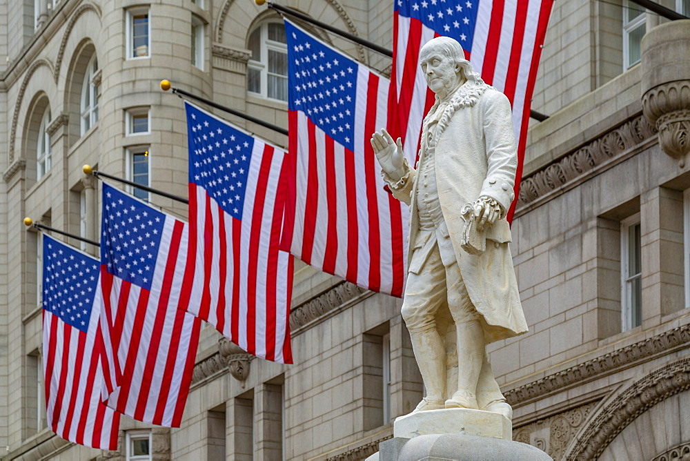 View of Benjamin Franklin statue and US flags in front of former Old Post Office Pavilion, Washington D.C., United States of America, North America
