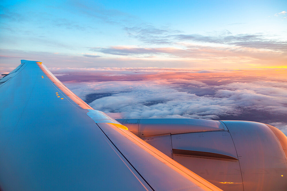 Generic view from airplane window of airplane wing and sunrise over England, United Kingdom, Europe