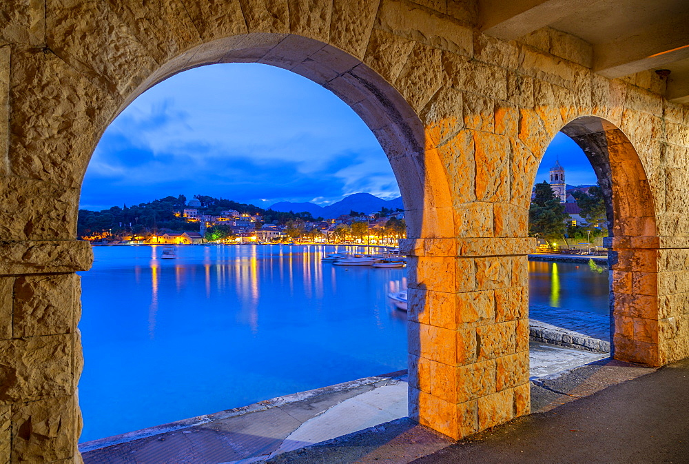 View of town and Crkva Sv.Nikole church through arches at dusk, Cavtat on the Adriatic Sea, Cavtat, Dubronick Riviera, Croatia, Europe