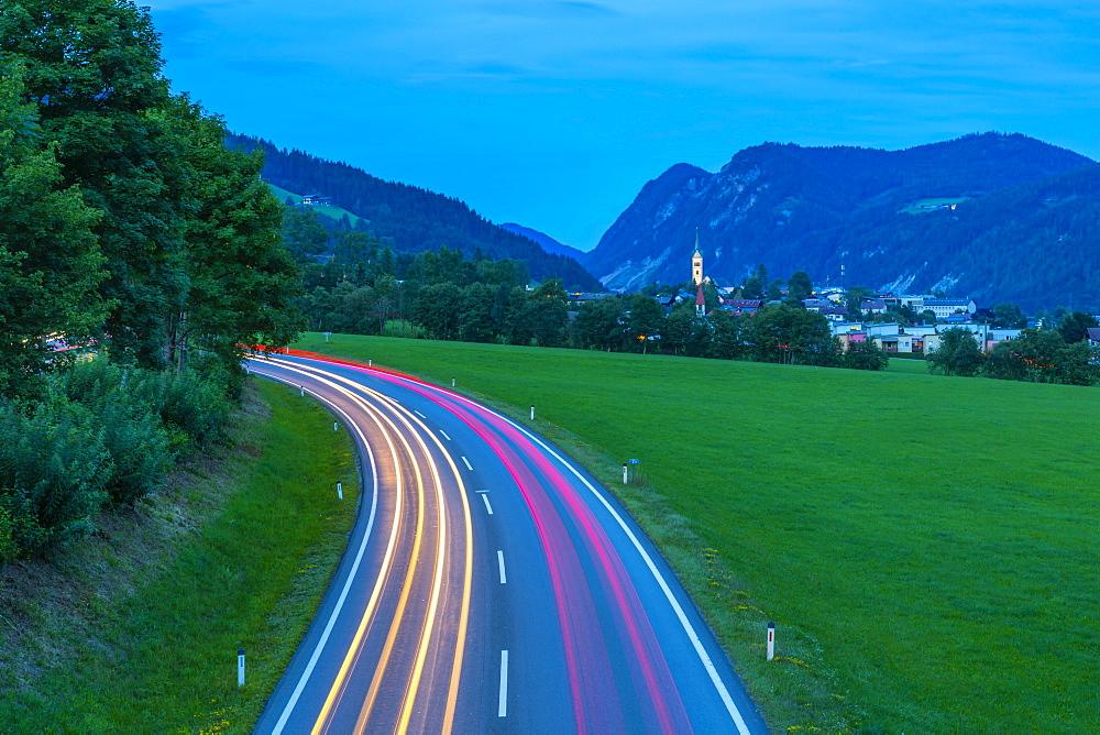 Trail lights and illuminated church in Radstadt at dusk, Radstadt, Styria, Austria. Europe