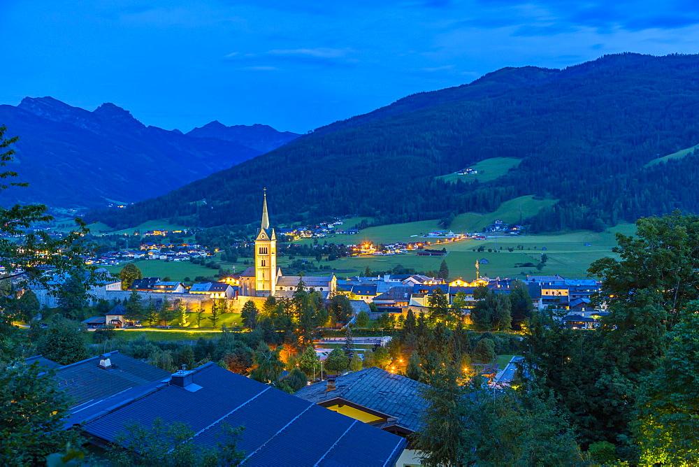View of illuminated church in Radstadt at dusk, Radstadt, Styria, Austria, Europe