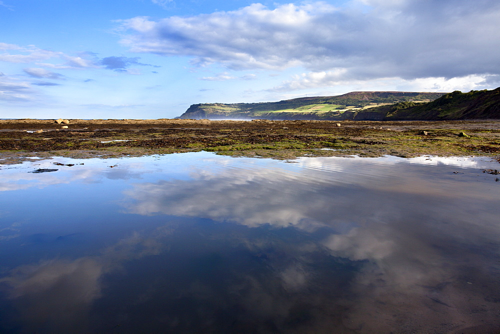 Cloud reflections in a tide pool at Robin Hoods Bay, Yorkshire, England, United Kingdom, Europe