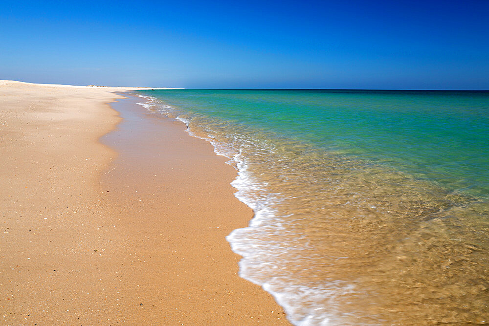 Empty white sand beach and breaking waves of crystal clear sea, Ilha do Farol, Culatra barrier island, Olhao, Algarve, Portugal