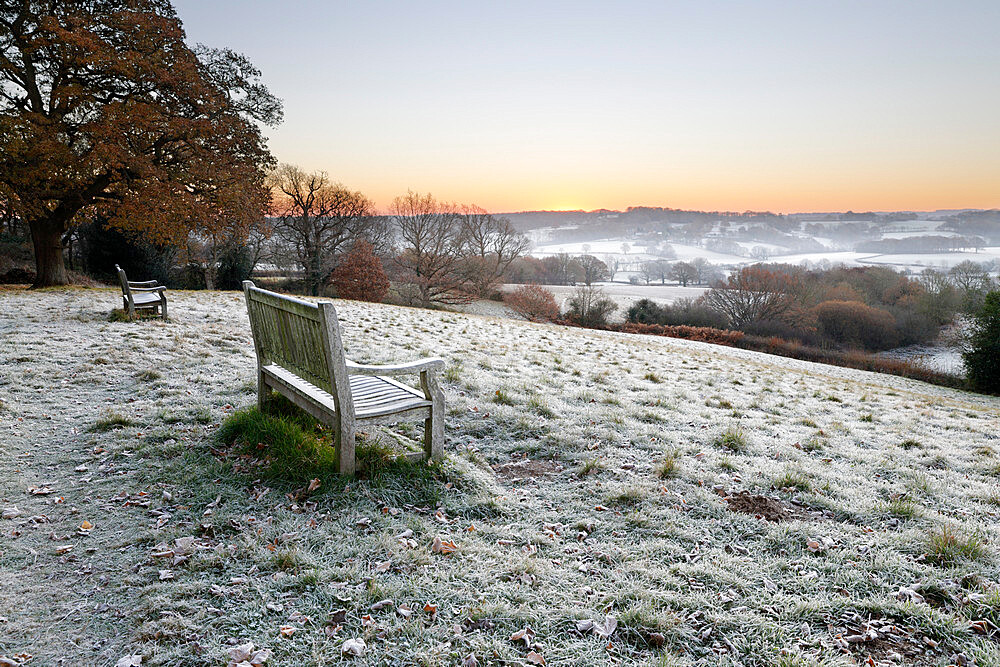 Wooden bench and view over Sussex landscape at sunrise in frost, Burwash, East Sussex, England, United Kingdom, Europe