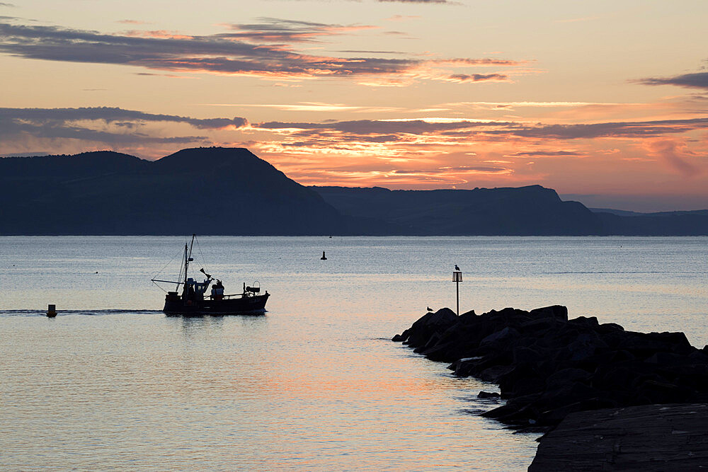 Fishing boat sailing past The Cobb at sunrise with Golden Cap and Jurassic Coast, UNESCO World Heritage Site, Lyme Regis, Dorset, England, United Kingdom, Europe - 846-2771