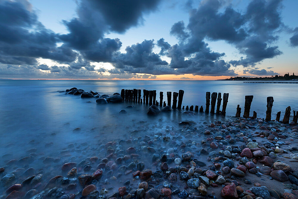 Old wooden piles going out to sea and pebbles on beach at dawn, Munkerup, Kattegat Coast, Zealand, Denmark, Scandinavia, Europe - 846-2783