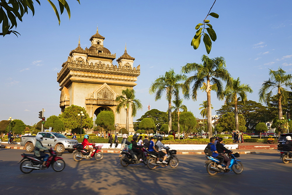 Mopeds riding past the Patuxai Victory Monument (Vientiane Arc de Triomphe), Vientiane, Laos, Indochina, Southeast Asia, Asia