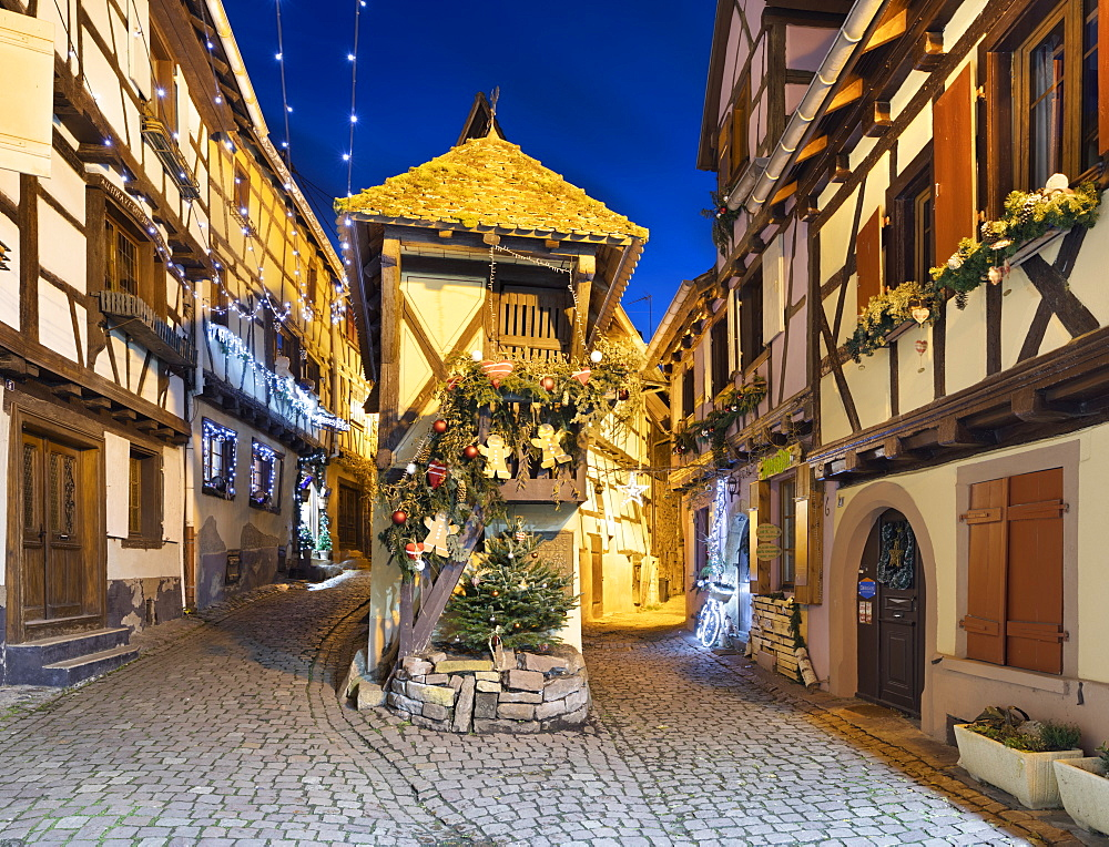Half-timbered houses along Rue du Rempart Sud lit up with Christmas decorations at night, Eguisheim, Alsace, France, Europe