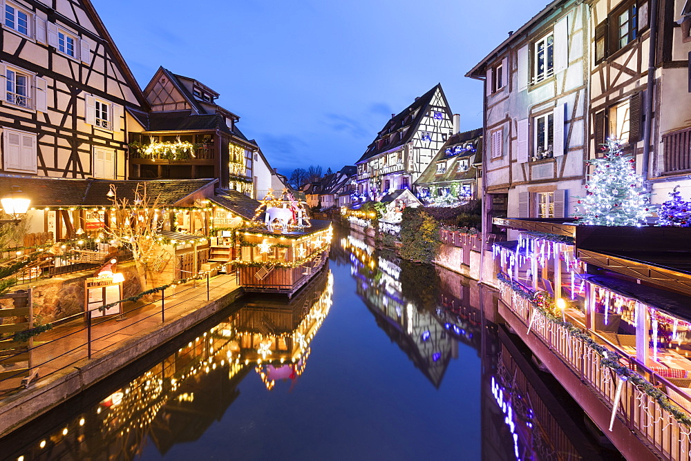 Christmas decorations on old buildings along La Lauch river in the Little Venice area at night, Colmar, Alsace, France, Europe