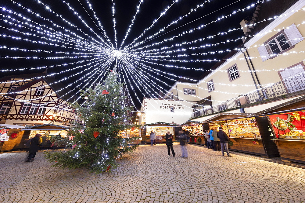 Christmas market with stalls illuminated at night at the Place Fernand Zeyer, Riquewihr, Alsace, France, Europe
