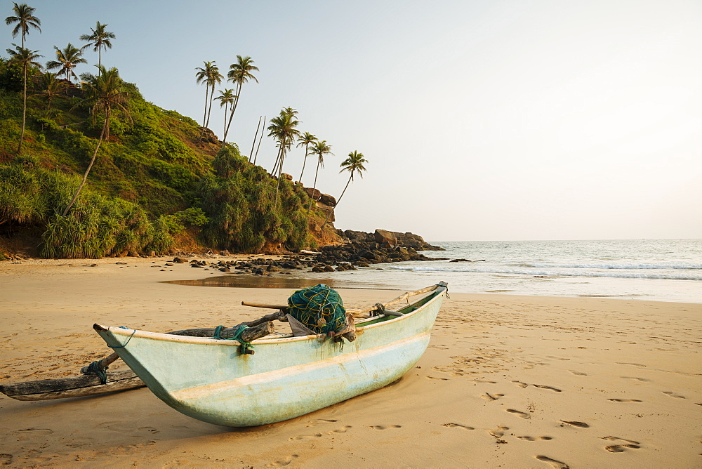 Traditional wooden boat on Talalla Beach at dusk, South Coast, Sri Lanka, Asia