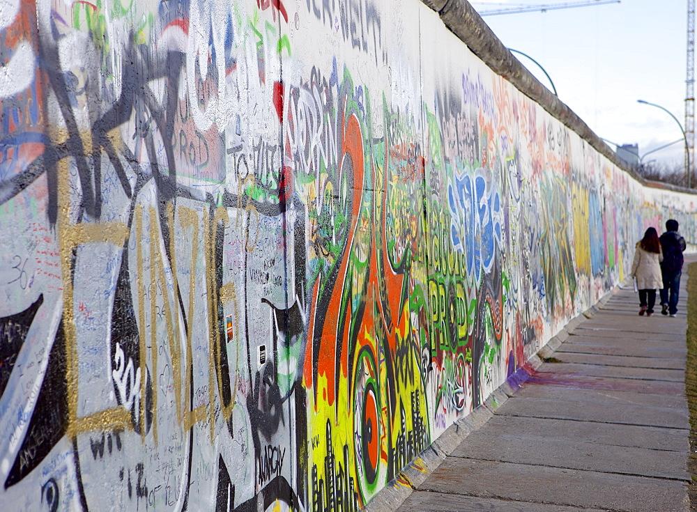 Couple walking along the East Side Gallery Berlin Wall mural, Berlin, Germany, Europe
