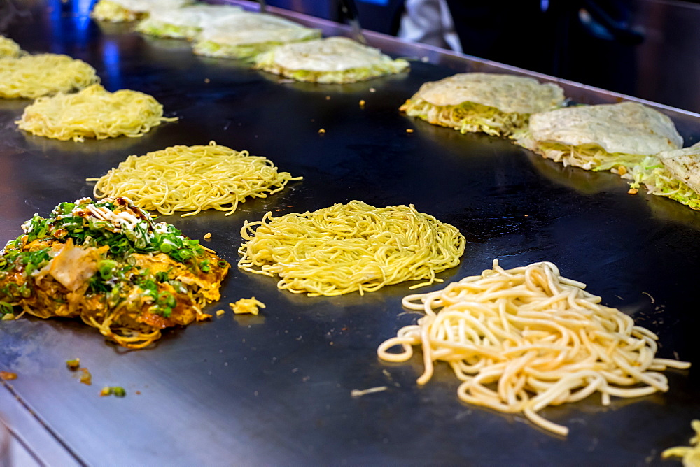 Okonomiyaki being prepared on a large griddle, Hiroshima, Japan, Asia