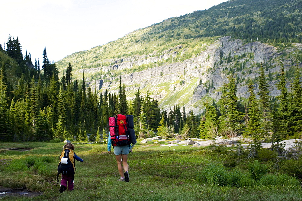 Mother and daughter backpacking through a meadow in a wilderness area.