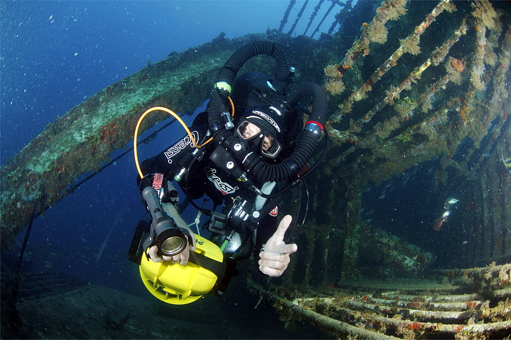 Mixed gas rebreather diver using scooter for mobility inside wreck.  Red Sea.
