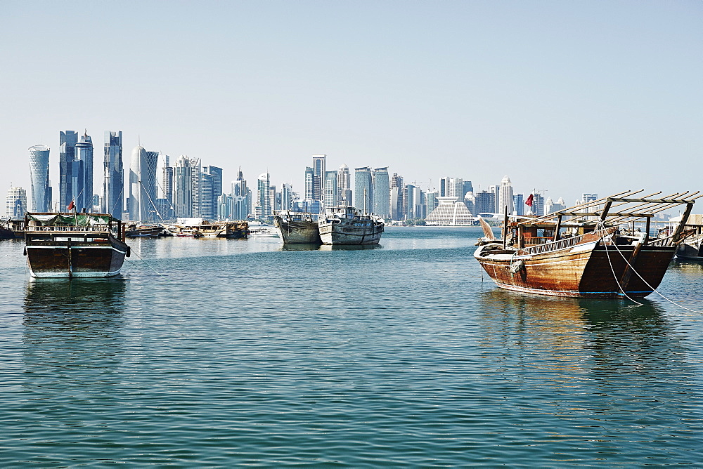 Downtown Doha with its impressive skyline of skyscrapers and authentic dhows in the bay, Doha, Qatar, Middle East - 975-257