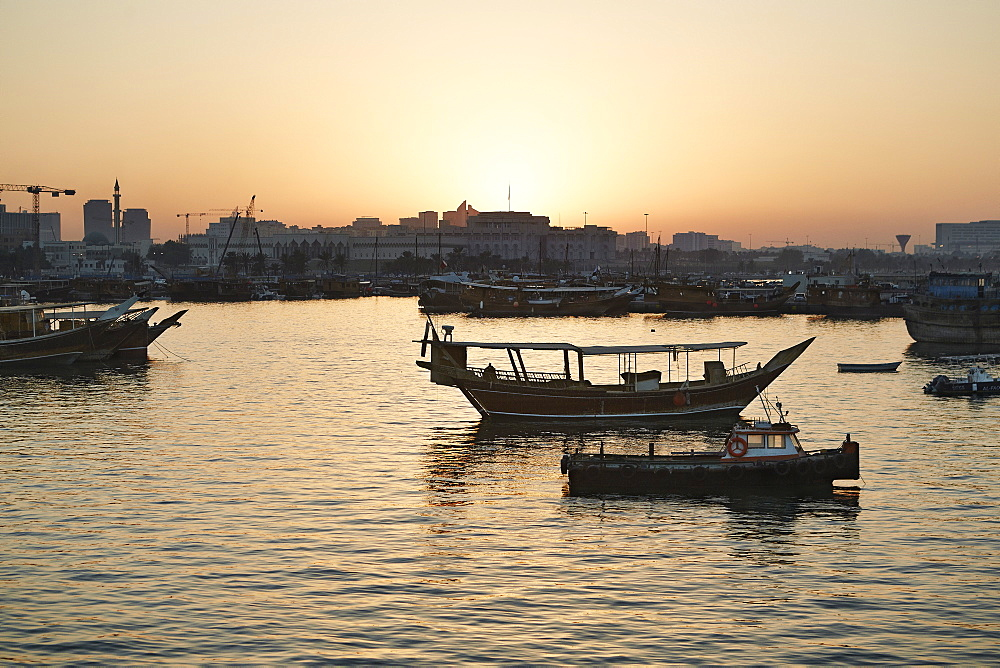 View from the Museum of Islamic Arts towards the old part of Doha and the dhows moored in the Harbour, at sunset, Doha, Qatar, Middle East