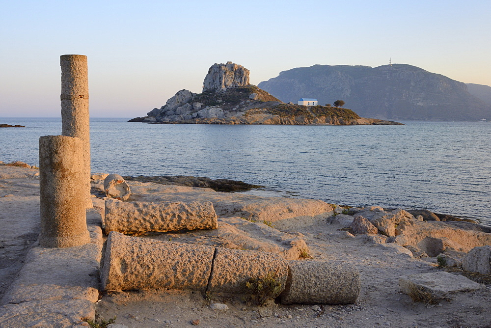 Basilica of Agios Stefanos ruins with Kastri islet and Chapel of St. Nicholas in the background at sunset, Kos, Dodecanese, Greek Islands, Greece, Europe
