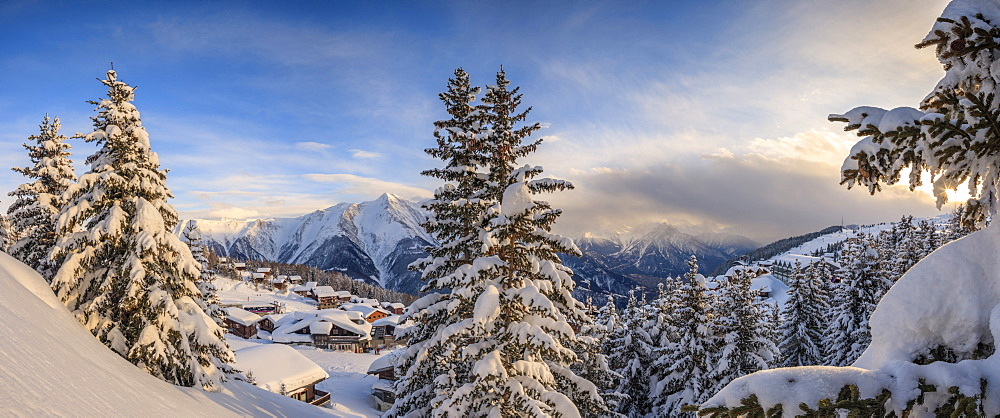 Panorama of snowy woods and mountain huts framed by sunset, Bettmeralp, district of Raron, canton of Valais, Switzerland, Europe