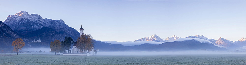 Panorama of St Coloman Church surrounded by the autumn fog at sunrise Schwangau Bavaria Germany Europe