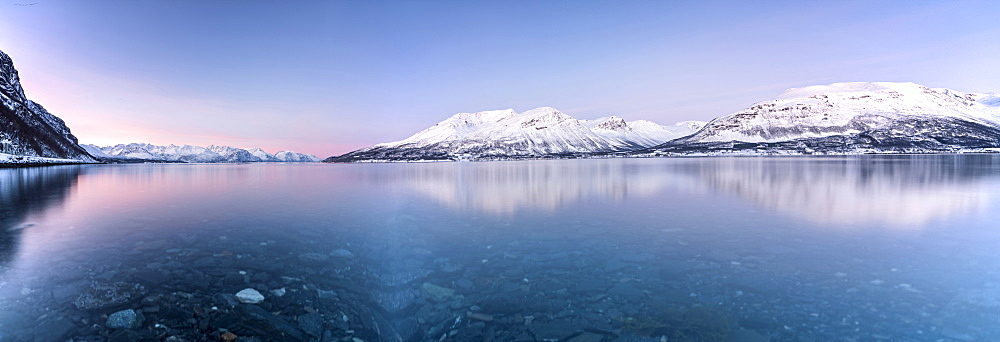 Panorama of pink sky and snowy peaks reflected in the frozen sea at sunset, Manndalen, Kafjord, Lyngen Alps, Troms, Norway, Scandinavia, Europe