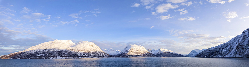 Panorama of snowy peaks surrounded by frozen sea Olderdalen Kafjorden Lyngen Alps Tromsø Norway Europe