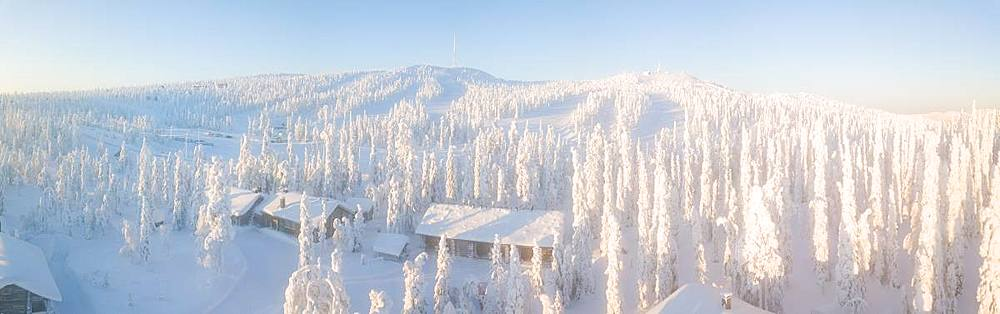 Elevated panoramic view of huts in the snow covered woods, Pallas-Yllastunturi National Park, Muonio, Lapland, Finland (Drone)